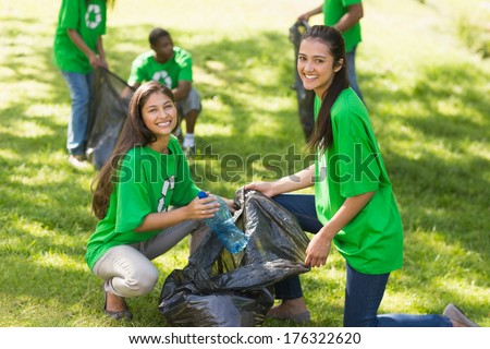 Team of young volunteers picking up litter in the park #176322620