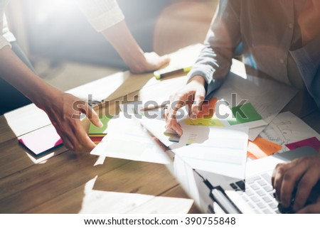 Team partnership. Photo young business managers  working with new startup project in office. Analyze document, plans. Generic design notebook on wood table, papers, documents. Horizontal, blurred