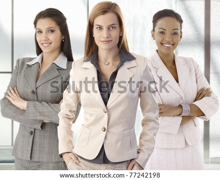 Team portrait of happy businesswomen standing on office corridor, looking at camera, smiling.?