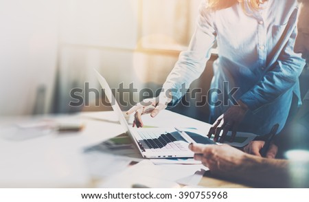Team project. Photo young talent managers working with new startup project in modern office. Generic design notebook on wood table. Horizontal, sunset effect, blurred