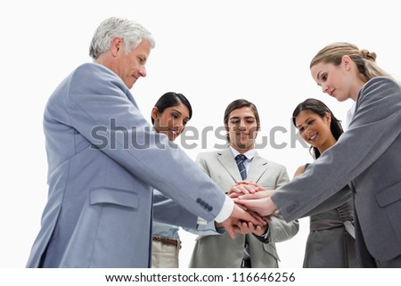 Team putting their hands on each others against white background