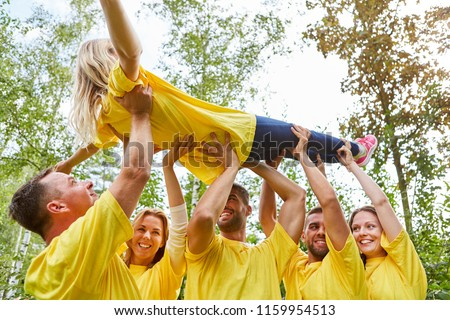 Team raises a woman together at a team building workshop #1159954513