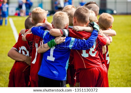 Team Sports for Kids. Children Sports Soccer Team. Coach Motivate Soccer Players to Play as a Team. Boys Kids Soccer Football Game. Young Children In Huddle Building Team Spirit.