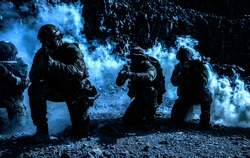 Team squad of special forces in action in the desert among the rocks covered by smoke screen under cover of darkness