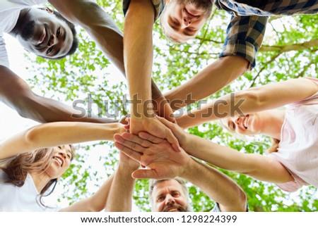 Team stacks hands in a workshop for teambuilding and teambuilding