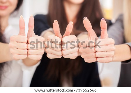 Team. Three business partners keeping thumbs up