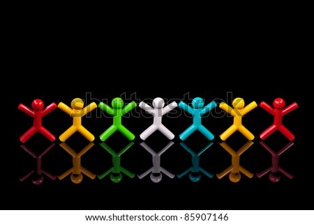 Team work concept. Colorful dolls on black background. - stock photo