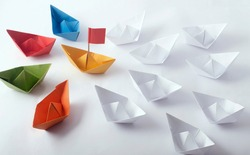 Team Work Concept using  different color Origami Paper Boats (ships)