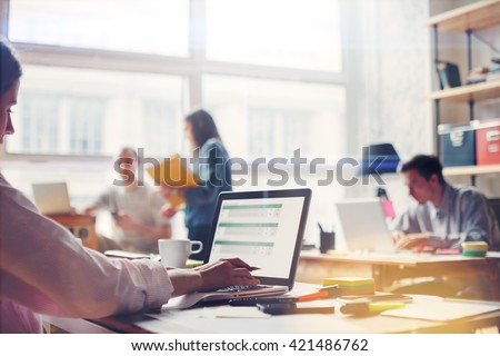 Team work process. Young business crew in big loft office. Laptop with graph, analysing marketing. Film effect, blurry background, lens flare effect
