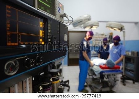 Team work with doctors, nurses, surgeons performing surgery on sick patient in hospital operation room. Focus on foreground