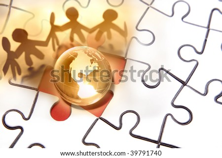 Team working together around globe on puzzle.