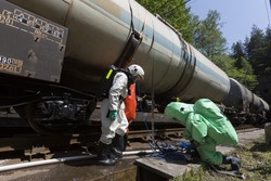 Team working with toxic acids and chemicals is securing train tanks crashed near Sofia, Bulgaria. Teams from Fire department are participating in a training with spilled toxic and flammable materials.