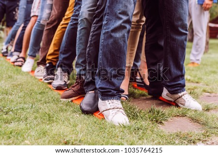 teambuilding exercises with bound legs on the grass jeans and shoes