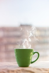 teaming coffee cup on a sunrise. window background