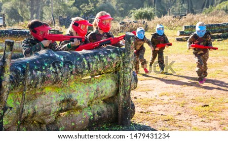 Teams of concentrated little kids facing on battlefield in outdoor paintball arena