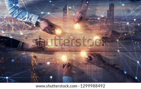 Teamwork and brainstorming concept with businessmen that share an idea with a lamp. Concept of startup. Double exposure