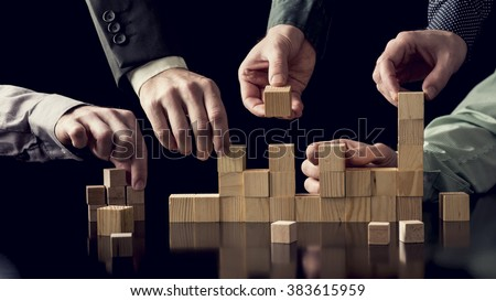 Teamwork and cooperation concept - five male hands building a structure of wooden blocks on black desk with reflection, toned retro effect.