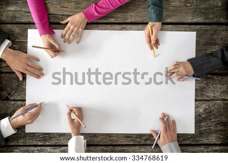 Shutterstock Teamwork and cooperation concept - top view of six people - men and women - drawing or writing on a large white blank sheet of paper.