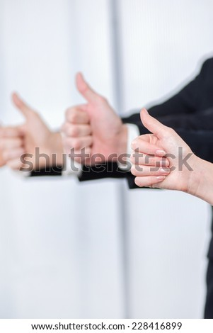 Teamwork and four thumbs up. Four smiling successful businessman showing thumbs up in a row