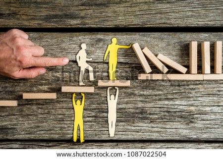 Teamwork and stopping the domino effect concept with paper cutouts of men supporting others on steps while they prevent a line of dominoes from falling. #1087022504
