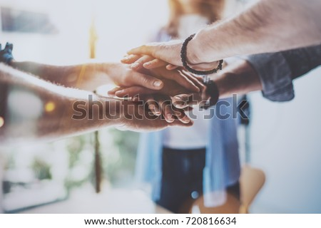 Teamwork business concept.Close up view of group of three coworkers join hand together during their meeting. Horizontal.Blurred background
