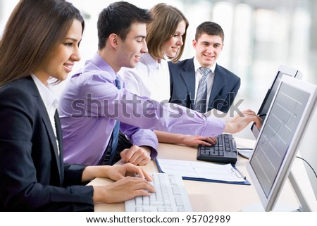 Teamwork - Business man showing something on computer screen to colleagues - stock photo
