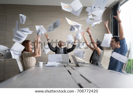 Teamwork business people excited happy smile, throw papers and documents fly in air. Success team concept after sign contract.In selective focus and motion blur moving with perspective view. Stock photo ©