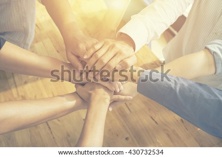 Teamwork concept,Business team standing hands together in the loft office.people joining  for cooperation success business,win in every thing,vintage color