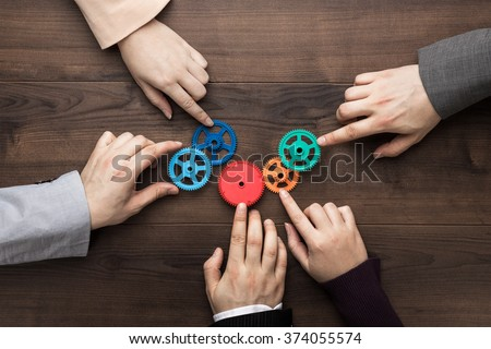 Photo of  Teamwork concept. Different hands of men and women connect colorful gears into working mechanism on the brown wooden table background. Each has its own role in problem-solving. Experience exchange