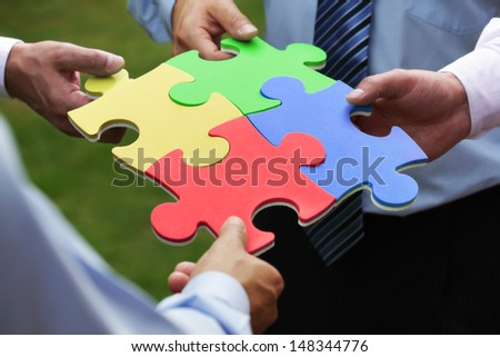 Teamwork concept four business people holding jigsaw puzzle pieces together