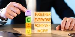 teamwork concept. man collects wooden blocks with the words together, everyone, achieves, more