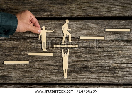 Teamwork concept on rustic wood with group of silhouette cutouts and a male hand helping a paper cutout of a climbing man. #714750289
