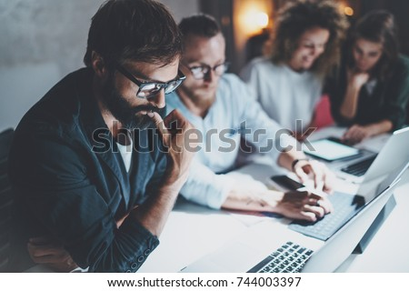 Teamwork concept.Project team making conversation at meeting room at night office.People using laptops and gadgets.Horizontal.Blurred background.Flares effect