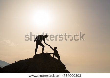 Teamwork couple helping hand trust silhouette in inspiring mountains. Team of climbers assistance man and woman hiker, help each other on top of mountain, beautiful sunrise landscape in Crete Greece #754000303