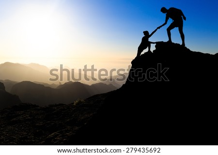 Teamwork couple hiking help each other trust assistance silhouette in mountains, sunset. Team of climbers man and woman hiker helping each other on top of mountain, climbing trust beautiful landscape.