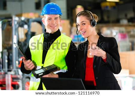 Teamwork - female supervisor and warehouseman or forklift driver with laptop and cell phone at warehouse of freight forwarding company - she pointing to the viewer
