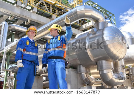 teamwork: group of industrial workers in a refinery - oil processing equipment and machinery