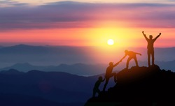 Teamwork helping hand trust assistance silhouette in mountains, sunset. Team of climbers man hiker, help each other on top of mountain, Business concept.