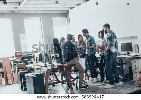 Teamwork in action. Full length of young modern people in smart casual wear discussing business while standing behind the glass wall in the creative office #583594417