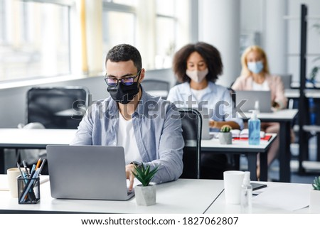 Teamwork in corporate company and returning to work after quarantine covid-19. Focused millennial man in glasses and protective mask works at laptop at workplace with antiseptic in office interior