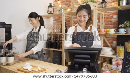 teamwork in startup successful small business cafe shop concept. two smiling women owners working in counter of restaurant. girl barista preparing coffee and coworker using tablet checking order.