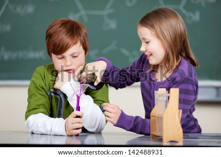 Teamwork in the chemistry class with a cute little girl pouring a chemical mixture into a funnel and test tube held by the boy