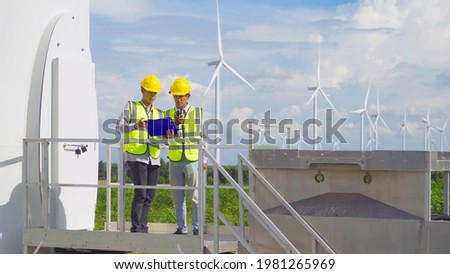Teamwork of Asian windmill engineer group, worker working on site at wind turbines field or farm, renewable clean energy source. Eco technology for electric power. industry nature environment. People Foto stock ©