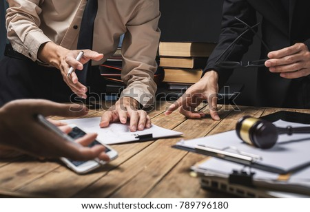 Teamwork of business lawyer meeting working hard about legal regislation in courtroom to help their customer.