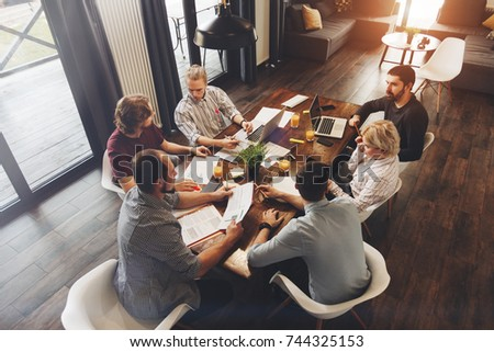 Teamwork on new business project in loft space. Group coworkers making great business decisions. Creative managers discussion work concept modern office #744325153