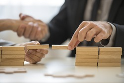 Teamwork or building bridges concept with a businessman and woman holding wooden building blocks to form a bridge over a gap while clasping hands in the background.