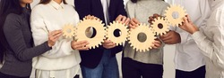 Teamwork, partnership, international cooperation concept. Hands of different ethnicity people business team or students friends holding various wooden gears as symbol of unity, support, common goals