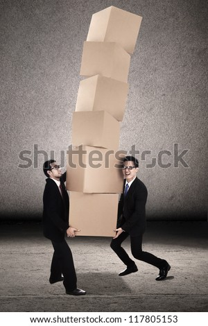 Teamwork photo concept: Two businessmen trying to balance plenty of boxes together
