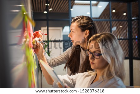 Teamwork, project management, agile methodology. Two young business women in the office are planning product development and support. Colleagues glue sticky stickers on the Board