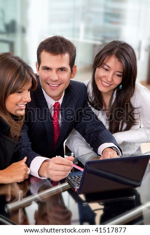 Teamwork smiling with a laptop at the office - stock photo